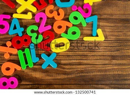 Colorful plastic numbers on a wooden table - stock photo
