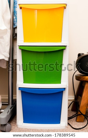 Colorful plastic storage crates in a bedroom - stock photo