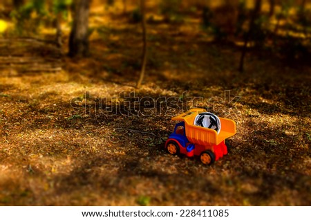 Colorful plastic toy truck and hardhat outdoors in the garden standing abandoned on the ground in the shade of a tree with copyspace - stock photo