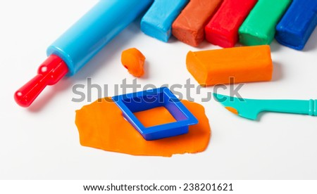 Colorful plasticine and tools on white background