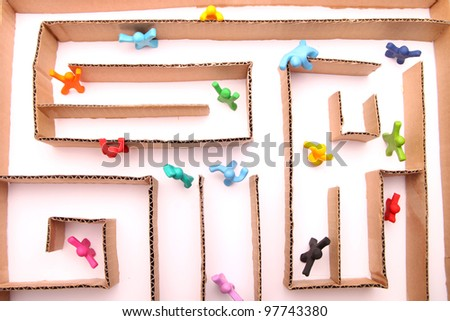 colorful plasticine people running puzzled through a labyrinth made of paper - stock photo