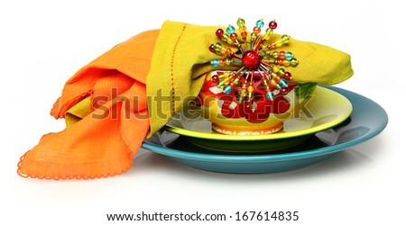 Colorful Plate setting over white background.  Plate, bowl, napkins. - stock photo