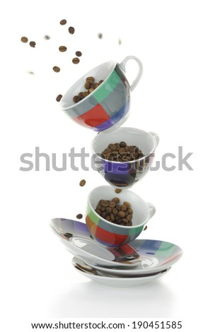 Colorful plates and cups with coffee beans isolated on white - stock photo