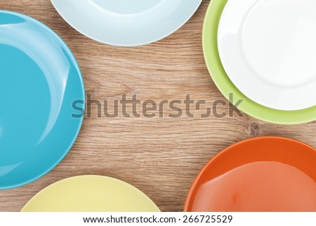 Colorful plates and saucers over wooden table background. View from above with copy space - stock photo