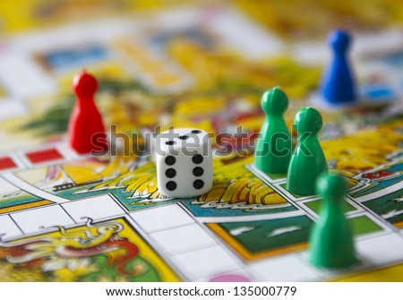 colorful play figures with dice on board - stock photo