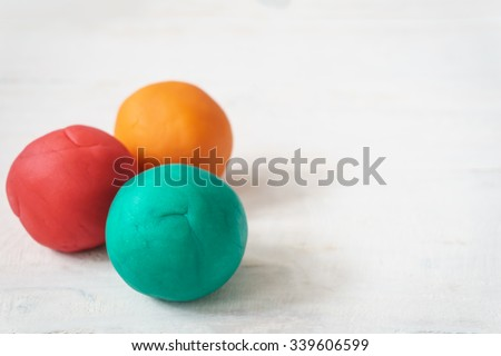 colorful playdough balls on wooden table. - stock photo
