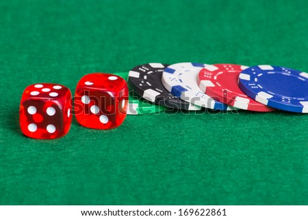 colorful poker chips and dice on a green casino felt