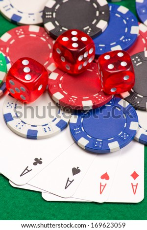 colorful poker chips, dice and four aces on the green table - stock photo