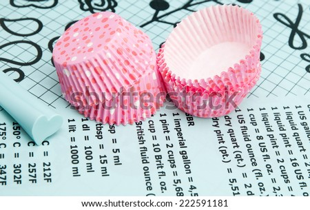 Colorful polka dot cupcake wrappers with color coordinated baking supplies . Closeup with shallow dof. - stock photo