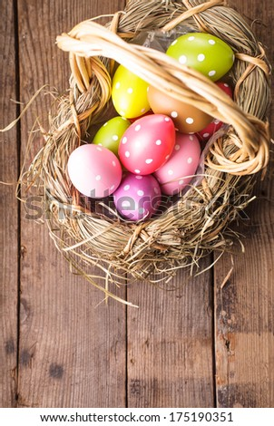 Colorful polka dot eggs in basket with copy space, Easter decorations - stock photo