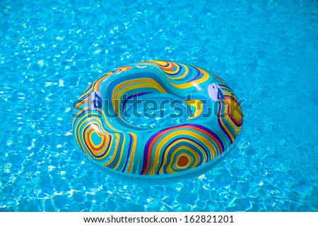 Colorful pool float in blue swimming basin - stock photo