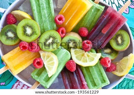 Colorful popsicles with fresh fruits in vintage tray - stock photo