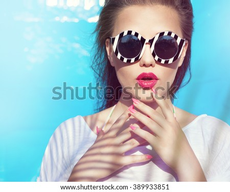 Colorful portrait of young attractive woman wearing sunglasses. Summer beauty and nail art concept - stock photo