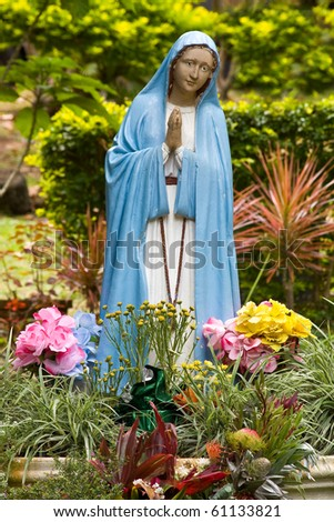 Colorful portuguese Virgin Mary statue in garden - stock photo