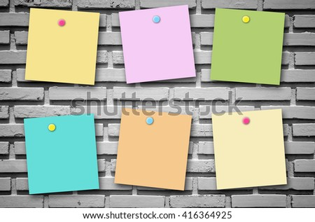 Colorful post it note on brick stone wall texture background.