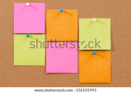 Colorful post it notes on cork bulletin board.