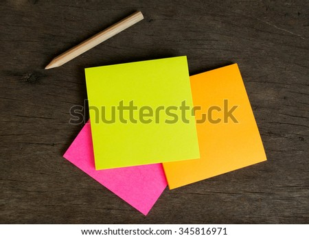 Colorful post note and pencil on wood board. Colorful post note have three color as yellow post note, pink post note , orange post note . Post note is object. People write in post note  - stock photo