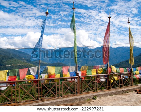 Colorful prayer flags over a clear blue sky near a temple in Bhutan with a view over the Himalayen mountains - stock photo