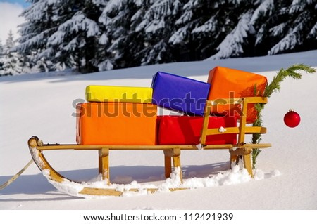 colorful presents on a Santa Claus sledge in a winter landscape - stock photo