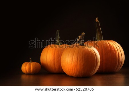 Colorful pumpkins on wood table with dark background - stock photo