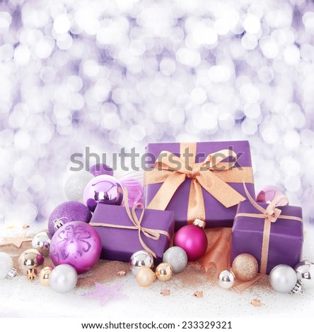 Colorful purple and gold Xmas gifts and baubles arranged in falling winter snow in square format with copyspace for your Christmas wishes or invitation to a seasonal party - stock photo