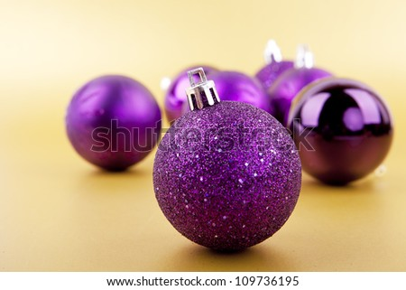 Colorful purple christmas decoration baubles on gold with space for text - stock photo