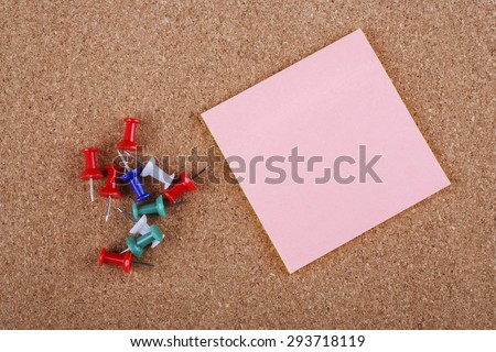 Colorful push pin with pink notepad on board background - stock photo