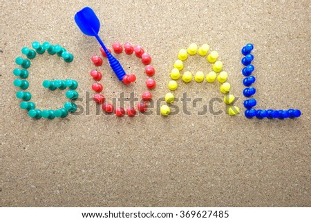 """Colorful push pins and blue dart with """"GOAL"""" word on a cork message board/bulletin board. Focus on red pins. Space for texts. - stock photo"""