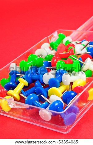 Colorful Push Pins on a red background