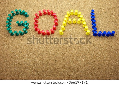 """Colorful push pins with """"GOAL"""" word on a cork message board/bulletin board. Focus on pins. Space for texts. - stock photo"""