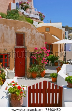 Colorful quiet backyard with beautiful flowers and classic traditional architecture in Santorini, Fira, Greece - stock photo