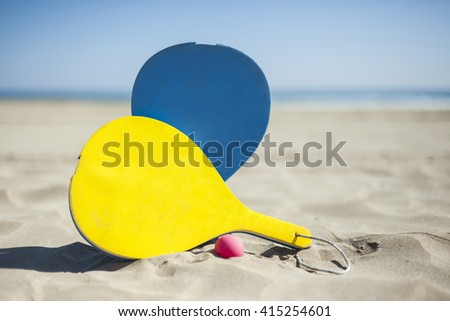 Colorful rackets and a ball in the sand of the beach in a sunny day. Summertime. Valencia, Spain. - stock photo