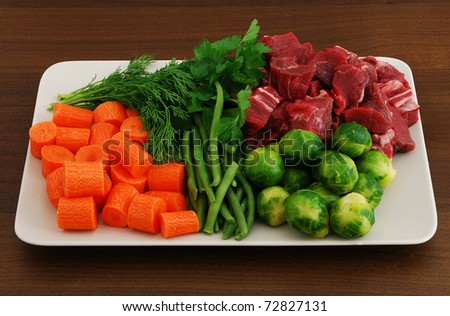 Colorful ragout ingredients including meat, carrot, Brussels sprouts, green beans and dill, organized in accurate piles on rectangular grey ceramic dish - stock photo
