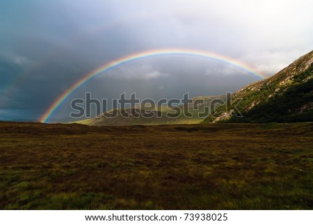 colorful rainbow at the sky over a meadow - stock photo