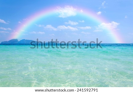Colorful rainbow over a Tropical beach of Andaman Sea, Thailand. - stock photo