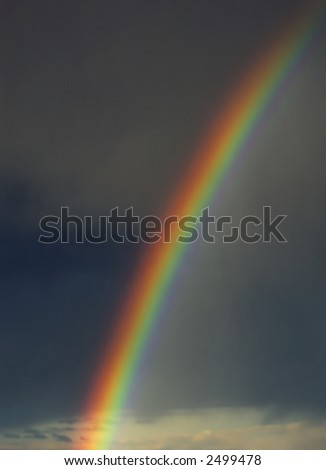 Colorful rainbow with dark storm clouds in background - stock photo