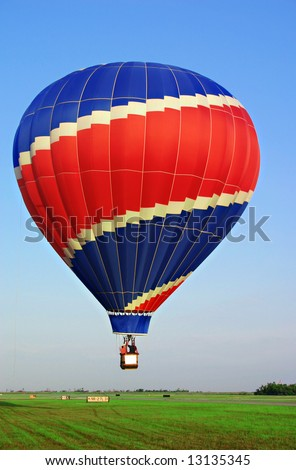 Colorful, red & blue, hot air balloon on a green grass field. - stock photo