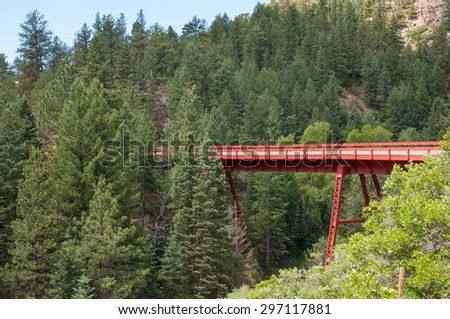Colorful red bridge along the Phantom Canyon Road in Colorado. - stock photo