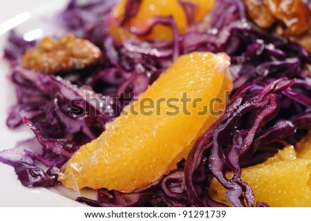 Colorful red cabbage salad with orange wedges, walnuts and olive oil - stock photo