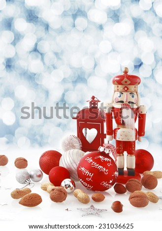 Colorful red Christmas still life of a traditional wooden nutcracker in the form of a king amongst assorted fresh nuts, baubles and a Xmas lantern in winter snow with a bokeh of falling snow behind - stock photo