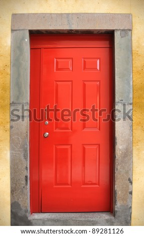 Colorful red door on rough wall - stock photo