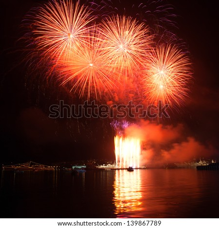 Colorful red fireworks in the night sky - stock photo