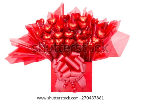 Colorful red gift of heart-shaped chocolate flowers in decorative cellophane tied with a bow for a loved one or sweetheart on Valentines Day, anniversary or Mothers Day, isolated on white - stock photo