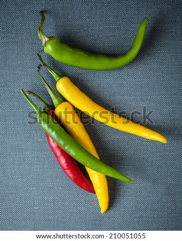 Colorful red, green and yellow chili peppers used in cooking as a spice for their punget hot flavor on a grey textile background - stock photo