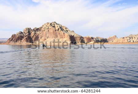 Colorful red, orange and white sandstone cliffs, rock formations, canyons and islands make Lake Powell an interesting location to study geology - stock photo