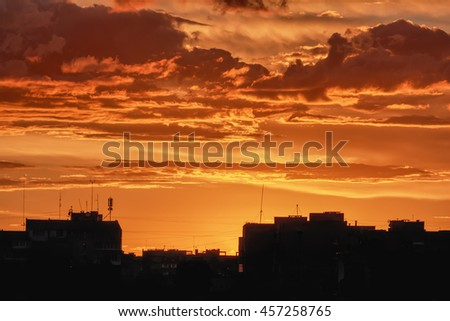 Colorful red sky during sunset time with street roofs.
