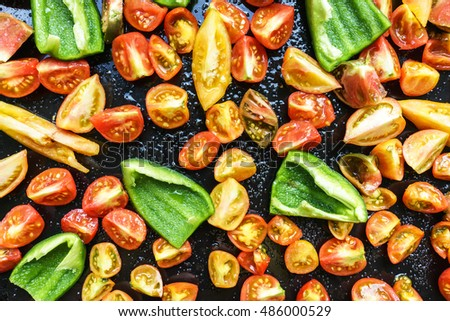 Colorful Red Tomatoes And Green Paprika Half Cutted On The Baking Tray And Ready For Roasting In The Oven With Thyme And Spices. Ready Food Vegetable Background.