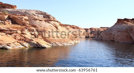 Colorful red, white, and orange sandstone cliffs and rock formations along shores of Lake Powell in southern Utah and northern Arizona - stock photo