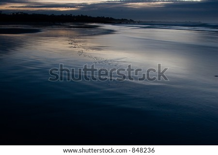 Colorful reflections on a beach at sunset - stock photo