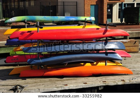 Colorful rental kayaks are stacked on the dock, Inner Harbor, Baltimore, MD - stock photo